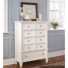 Finished in crisp white with satin nickel drawer pulls, this beautiful 5-drawer chest combines contemporary design with functional organization. Styled with sleek mouldings and ornate feet, this beautiful chest is a signature design by Ashley furniture.