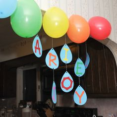 Noah's Ark Birthday Party Raindrop Name with photo on the back hanging from thread on archway. Rainbow balloons above the archway finish the look.