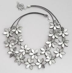 Dos filas de flores plata hace este collar un artículo excepcional. Las flores son de 2.2 cm de diámetro. También puede colocar la forma que desee, separadas o juntas. Cuelgue de una cadena de cuero y cierre con un broche de omega. Puede solicitarse en color dorado.