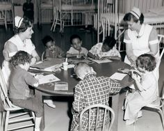 Nursing students sit with children as they color and craft - 1960