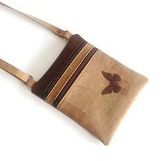 This unique and practical small cross body bag has been handmade from genuine portuguese cork. Has plenty of room inside to hold all your essential items making it perfect for everyday use. You can also use it as a hands free travel purse to carry your passport, phone, wallet, sunglasses... Also makes a great, unique and eco friendly gift for a friend! This bag has one main zipper, a zippered pocket and an adjustable strap. It is lined with a matching 100% cotton fabric and fully interfaced…