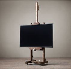 RH's 19th C. English Artist's Easel - Coffee:The simplicity and strength of a 19th century artist's easel inspired this support for modern media or artwork. Crafted from solid oak, it holds a flat screen television much as the original held a canvas – clamped between brackets that can be raised and lowered by a crank to the optimal viewing height. A turn-key locks the castors.