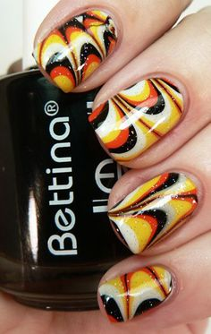 Halloween colors inspired marble nail art. Combine popular Halloween polish colors such as orange, red, black, white and yellow to form eccentric patterns on the nails which are pleasing to the eye.
