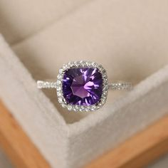 This halo ring features a 8*8mm cushion cut natural amethyst and sterling silver finished with rhodium. Customization is available. It is made by hand, and it will take about 7 days to finish the ring after your payment is completed. Main stone: natural amethyst Amethyst weight: Approx 2.10 ct Metal type: sterling silver finished with rhodium Accent stone: cz  Customization is available, I also can make it with 14k solid gold (white or yellow or rose) and diamond accent stone, just feel free…