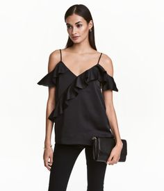 Black. Top in woven fabric with wide ruffles, narrow adjustable shoulder straps, and V-neck at front and back. Lined.