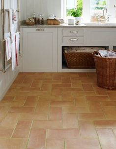 Alicante terracotta tiles laid in a herringbone pattern gives a modern twist to this traditional material. Mandarin Stone