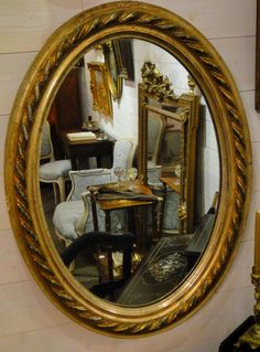 Very pretty #oval mirror #Restoration in gilt wood and stucco, from the first half of the 19th century, decorated with ribbon. The twisted ribbon has silver highlights on its round parts. Mercury glass and #vintage #gold leaf gilding. For sale on Proantic by AAA - Art & Antique Addicts.