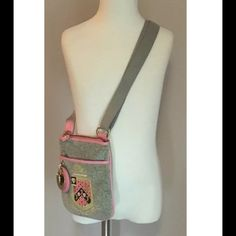 """Juicy Couture girls cross body velour handbag • All over gray velour • Stitched gold, pink logo design on front  • Trimmed in pink  • 3 charms hanging from side: 1 gold heart, 1 round gold medallion with crown and 1 round pink """"leather"""" circle with juicy logo embossed • 1 outside pocket  • zip closure • Adjustable strap • Pink heart on back with stitched """"J"""" • 2 compartments inside • Heart zipper pull • Measures 8"""" long and 6"""" wide • Strap measures 20"""" at its longest • Can be adjusted from…"""