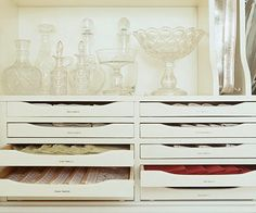 Shallow drawers for flatware are ideal for storing linens. Sort tablecloths, runners, and napkins by color. Labeling the drawers reduces search time.