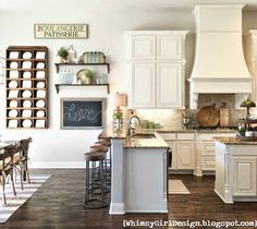 Whimsy Girl Design Blog kitchen, dark hardwood floors, plate rack, DIY shelves, chalkboard, white cabinets, vent hood, tumbled travertine backsplash, farmhouse style, rustic kitchen.