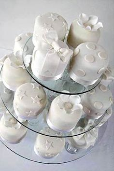 Rolled fondant white mini wedding cakes, decorated with fondant polka dots, stars, bows and flowers - from www.maisiefantaisie.co.uk