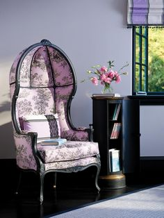 This chic, dome-shaped reading chair features a feminine lovely pink-and-black patterned fabric. The purple room is decorated with pink flowers and a small bookcase.
