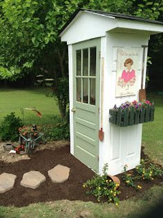 Shed made from old doors.  This would be so cute as a potting shed.
