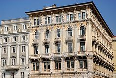 Photo made at Model Palace in Piazza Unità d'Italy in Trieste, Friuli Venezia Giulia (Italy). In the picture you see, in the foreground, the right side, full of balconies and statues on the top floor of the front and side of the historic building model, the left is part of the central facade. Above the rooftops you can see the blue sky.