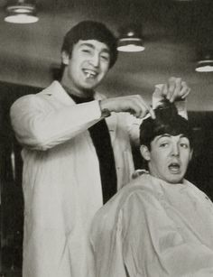 Dezo Hoffman, 1912 -1982  Title: Lennon, cigarette clenched in smiling teeth, wearing a white barber's jacket about to 'cut the hair' of Paul McCartney    Ref.#: 1   Medium: Gelatin Silver Print   Mount: unmounted  Print Date: 1964   Photo Date: 1964