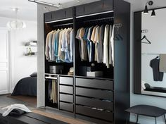 A modern bedroom with an open black-brown PAX wardrobe combination, STRIBERG wardrobe lighting and a black STAVE mirror