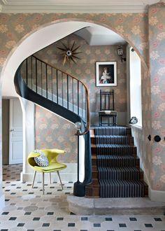 <p>En habillant les murs de papier peint et en ennoblissant d'un tapis les marches de cet escalier, cette cage d'escalier prend des allures majestueuses et contrastées.</p>