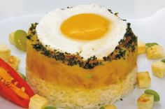 LOCRO DE ZAPALLO CON HUEVO: Preparación: Preparar el arroz graneado. Freír los huevos en aceite vegetal. En una olla, dorar en aceite vegetal la cebolla picada, los ajos y el ají amarillo molido. Incorporar el zapallo, las papas, las habas y los choclos cortados en rodajas.  Cocinar a fuego lento hasta que los alimentos estén cocidos; incorporar la leche, el queso, el huacatay y la sal yodada; mezclar todo y retirar del fuego. Servir el locro de zapallo, acompañar con arroz y huevo frito.