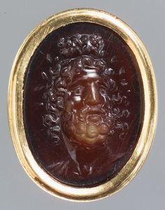 Gemme: Kopf des Serapis. Griechisch, Hellenistisch 2. Jh. v. Chr. Sard, klar durchscheinend. In moderner Goldfassung.