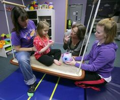 "In this Oct. 15, 2012 photo, Melissa Ehli, left, physical therapist assistant, sits with Maryjane ""MJ"" Luntz, 5, to help her with her posture while Registered Occupational Therapist Amy Tran, right, encourages her to place the peg in the correct hole as Speech Language Pathologist Partty Welling signs the word pink at Building Block Rehabilitation in Fairbanks, Alaska. Luntz has Rett Syndrome, a disorder of the nervous system that leads to developmental reversals."