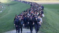 Uprchlíci za doprovodu policie procházejí Slovinskem.