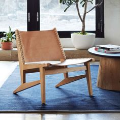 This wood-framed sling chair is made with raw, undyed leather that will only get better with wear.
