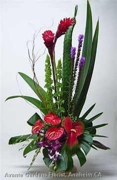 """A tropical design standing an impressive 40"""" tall, featuring ginger, anthuriums, liatris, orchids, Bells of Ireland, woven palms and a large variety of exotic foliages."""