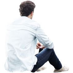 Man sitting on the ground and holding his cell phone in a forlorn, introspective manner.