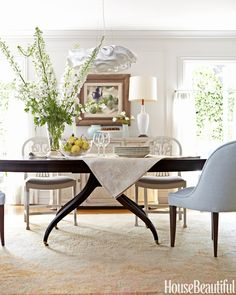 In a Corona del Mar, California, house, Barbara Barry took the edge off the dining room's formality with a Nevo pendant by Arturo Alvarez and a Swedish cabinet. The graceful curves of the vintage and custom chairs echo those of the 1940s table.