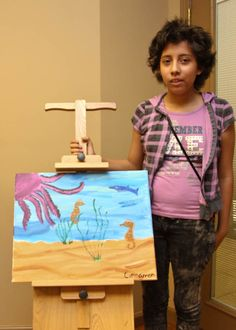 Wigs 4 Kids recipient Cinnamon showcasing the painting she created in our open studio art therapy classes.