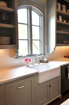 Sally Wheat    gray kitchen design with soft gray green kitchen cabinets painted Martha Stewart Fieldstone, calcutta marble countertops, subway tiles backsplash, farmhouse sink, open shelves and polished nickel hardware and faucet.