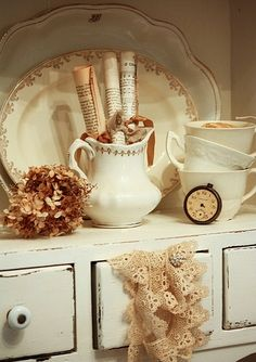 Creamy Vignette of textured touches: dried hydrangea, rolled book pages and music, pocket watch, scrap of favorite lace