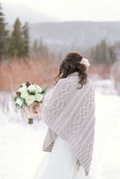 Bride walks in the snow to her winter elopement site in rocky mountain national park colorado