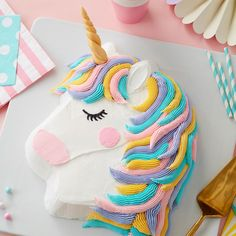 This Rainbow Unicorn Cake is ready for birthday fun! Complete with a colorful pastel mane and a gold fondant horn, this unicorn cake is great for birthday princesses of all ages. A great project for beginning decorators, this cake uses the pony pan to make this shaped cake.