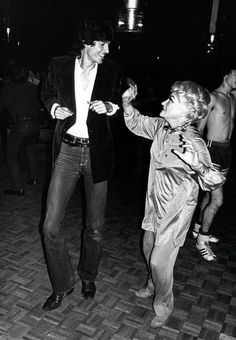 Broadway star Tommy Tune and comedienne Phyllis Diller shaking it up at Studio 54 as a waiter in his uniform of basketball shorts and sneakers heads the other way.