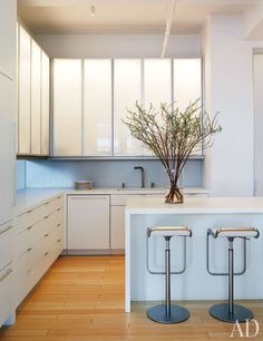 "Tracy and Nick Lehman called on architect (and neighbor) Katherine Chia of Desai/Chia Architecture to combine two New York City apartments. ""To live minimally you need ample, well-organized storage space,"" says Chia, who designed the kitchen with tall, illuminated anodized-aluminum-and-acrylic upper cabinets and Corian countertops and lower cabinets. The back of the island houses appliances and includes additional storage. (July 2011)"