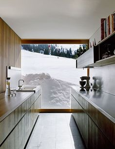 A sleek kitchen looks out onto a snow-covered mountain at a beautiful modern home in Austria