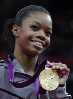 U.S. gymnast Gabrielle Douglas displays her gold medal during the gymnastics women's individual all-around competition.