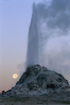 *White Dome Geyser erupts by a full moon at twilight.  (National Geographic)