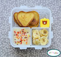 heart shaped french toast with syrup in container, applesauce with fall sprinkles, dried banana chips