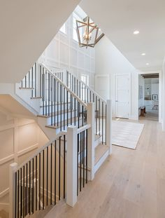 Iron spindles paired with painted white railings and posts + white square wainscoting on the walls + large gold lantern chandelier + white risers and wood treads on the stairs House Staircase, Staircase Remodel, Staircase Design, Staircases, Dream Home Design, House Design, Coastal Living Rooms, House Rooms, Interiores Design