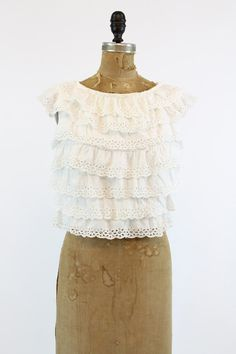 Super sweet 1970s eyelet blouse! Done in a bright white cotton with sweet eyelet cut outs. Seven layers of ruffles. Buttons down the back of blouse.