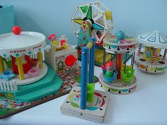 These are the oldest Fisher Price pieces that I have.  Three of the pieces are mainly wood and the two larger ones, the ferris wheel and the merry go round have wood bases.  All the graphics are in pretty decent shape.  Three wind up and play music too.