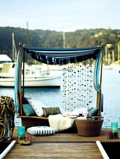 Relaxing day bed on a dock. Love the shell curtain.