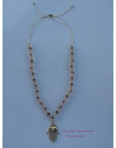 handmade macrame necklace with gold cord, crystal beads and dold hasmsa hand