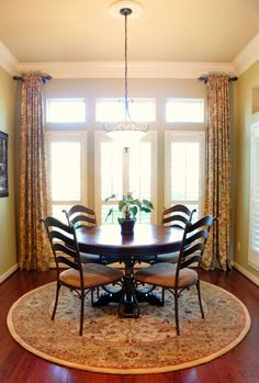 Nice breakfast room.  I like the way the drapes are hung (love those short rods!) and the plantation shutters.