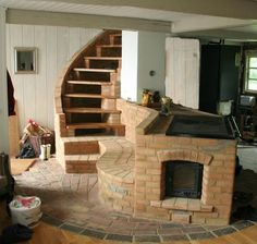 brick cookstove | Masonry heater and cookstove by feudebois.com. Flue gases heat the bench and warm the stairs before heading up the chimney.