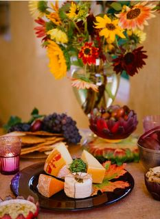Cheese, fruit, meats are excellent choices for Tuscan wedding appetizers. Pair with local mixed flowers, candles and wine for a visually dynamic tablescape.