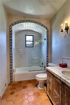 An arched alcove edged with artisan tile surrounds the tub shower in a secondary bathroom. Note rustic cabinetry, Saltillo tile floor and white glazed-tile countertop.