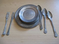Antique part of pewter dinnerware, 1 large plate, 2 forks and 3 knives